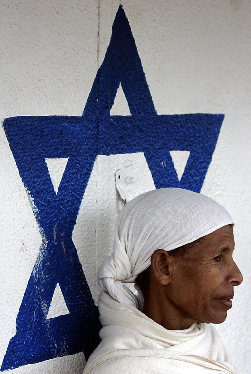 . BEER SHEVA, Israel:  Zbainish, 67-years-old, an Ethiopian Fellasha immigrant, stands next to a painted blue David star 15 February 2006 in the Nurit absorption centre in Beersheva, southern Israel. Zbainish arrived over a year ago and lives in the center with other hundreds of Ethiopians before starting a new life in Israel. There are some 100,000 Ethiopian Jews living in Israel and unlike most Jews in the diaspora, who are granted Israeli citizenship automatically upon arrival, Ethiopia\'s Jews needed the Jewish state\'s rabbinate to recognise them as Jews in 1975 before being allowed to enter the country. MARCO LONGARI/AFP/Getty Images