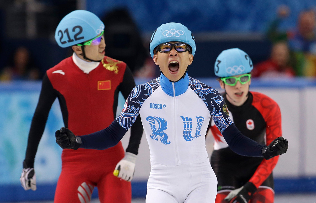 . Victor An of Russia, centre, reacts as he crosses the finish line ahead of Wu Dajing of China, left, and Charle Cournoyer of Canada in the men\'s 500m short track speedskating final at the Iceberg Skating Palace during the 2014 Winter Olympics, Friday, Feb. 21, 2014, in Sochi, Russia. (AP Photo/Darron Cummings)