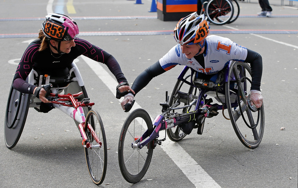 . Third place finisher Manuela Schar, left, of Switzerland and women\'s wheelchair winner Tatyana McFadden, of the United States, celebrate after completing the New York City Marathon, Sunday, Nov. 3, 2013, in New York. (AP Photo/Kathy Willens)