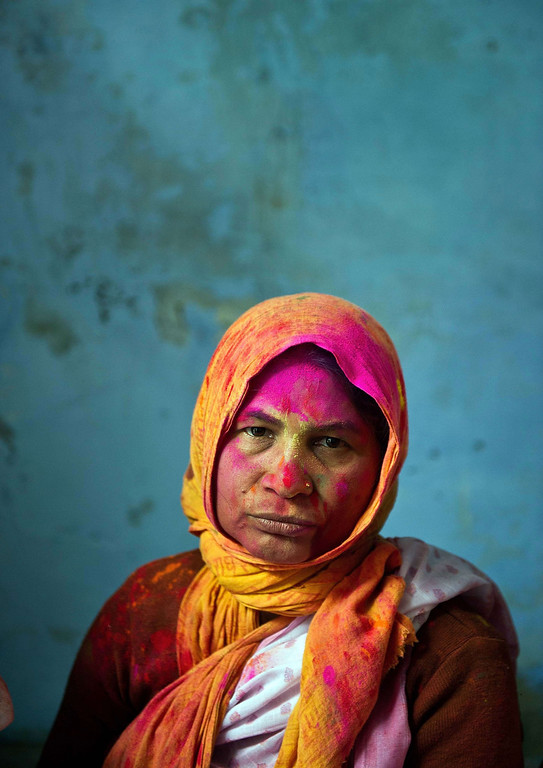 . An Indian widow, seen smeared with colored powder, rests after celebrating Holi in Vrindavan on March 14, 2014.   AFP PHOTO/Prakash SINGH/AFP/Getty Images
