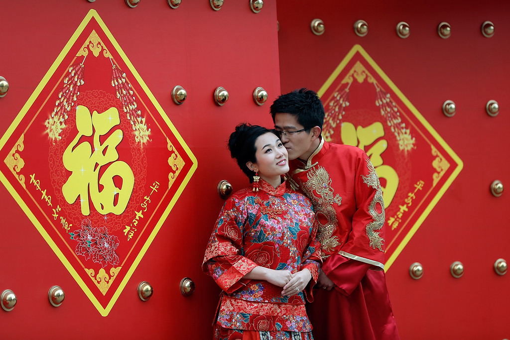 . A couple dressed in traditional Chinese costumes have wedding portraits made on Valentine\'s Day February 14, 2013 in Beijing, China. Young Chinese couples have embraced the Western concept of Valentine\'s Day with hawkers selling roses and chocolates.  (Photo by Lintao Zhang/Getty Images)