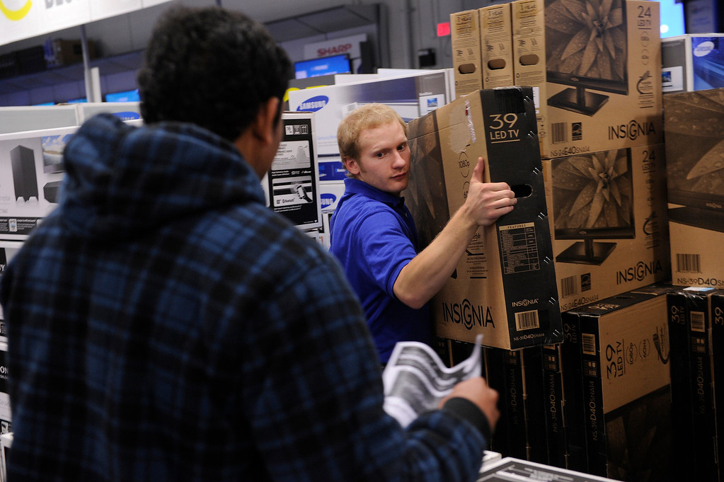 . Best Buy associate Christopher McNair delivered a television for a customer Thursday night. Shoppers lined up for deals at the Best Buy store in Lone Tree Thursday night, November 28, 2013. Best Buy remained open thought the night. Photo By Karl Gehring/The Denver Post