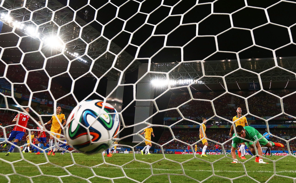 . Jorge Valdivia of Chile (obscured) shoots and scores his teams second goal against goalkeeper Mathew Ryan of Australia during the 2014 FIFA World Cup Brazil Group B match between Chile and Australia at Arena Pantanal on June 13, 2014 in Cuiaba, Brazil.  (Photo by Matthew Lewis/Getty Images)