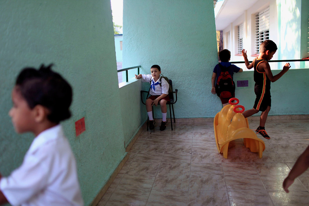 . Cristian Vazquez watches his friends play as he waits for his teacher at the Dora Alonso school in Havana, Cuba on May 16, 2013. Six-year-old Vazquez was diagnosed with autism in 2008 and began attending this special school that caters to the education of children with autism. Although Vazquez\'s education is paid for by the state, his parents say that it is difficult to acquire special materials for their son, like books that have figures, colors and pictograms. (AP Photo/Franklin Reyes)