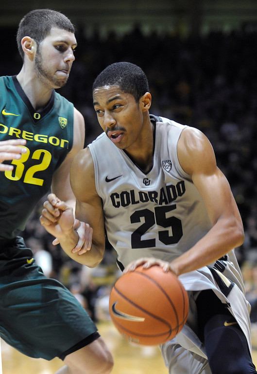. BOULDER, CO. - MARCH 7: Colorado point guard Spencer Dinwiddie (25) made a move past Oregon forward Ben Carter (32) in the second half. The University of Colorado men\'s basketball team defeated Oregon 76-53 Thursday night, March 7, 2013 at the CU Events Center in Boulder. (Photo By Karl Gehring/The Denver Post)