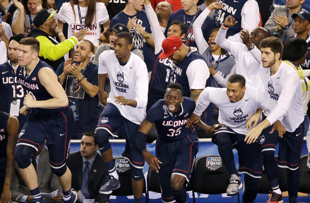 . Connecticut players celebrate at the end of an NCAA Final Four tournament college basketball semifinal game against Florida Saturday, April 5, 2014, in Arlington, Texas. Connecticut won 63-53. (AP Photo/Tony Gutierrez)