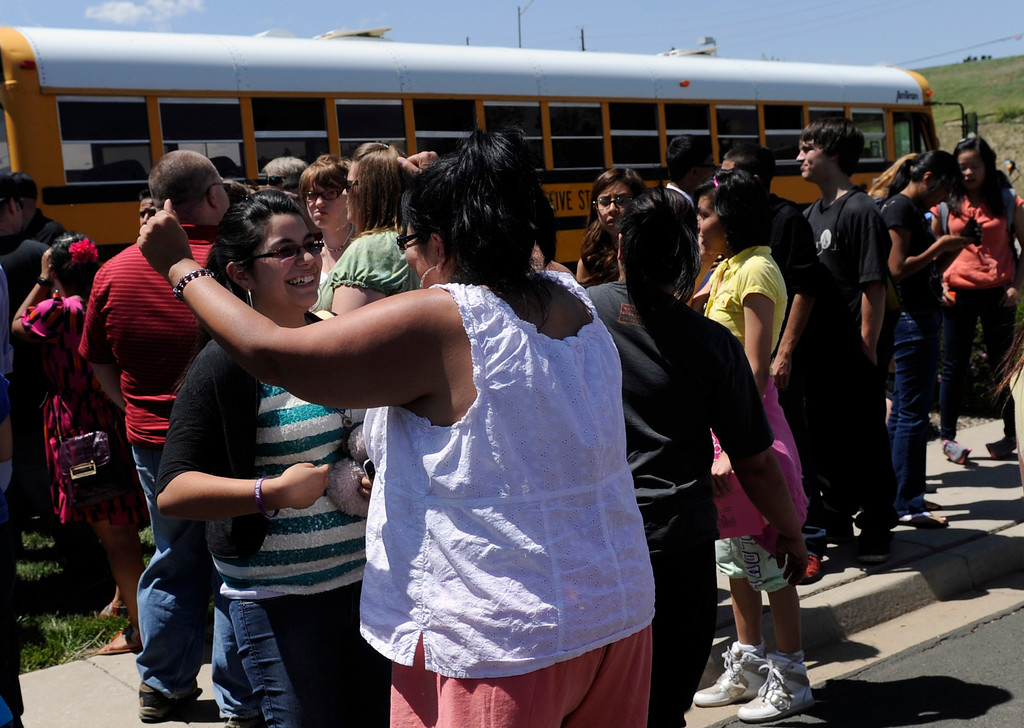 . Vida Zamora (center in white) is very happy to see her daughter Dakota, 17, as she gets off the bus after being evacuated from Thornton High School. Parents of Thornton High School students meet their children a few blocks from the school after Thornton police evacuated the school when they received a report of two people with a gun on campus. (Photo By Kathryn Scott Osler/The Denver Post)