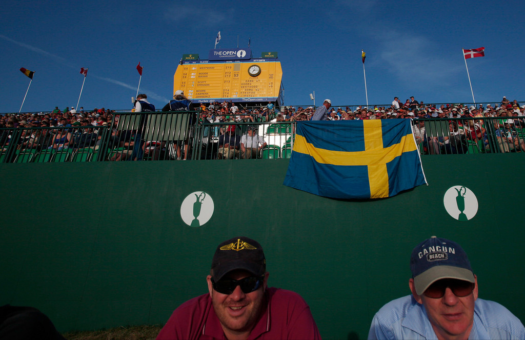 . Two spectators sit under a Swedish flag on the 18th green during the third round of the British Open Golf Championship at Muirfield, Scotland, Saturday July 20, 2013. (AP Photo/Jon Super)