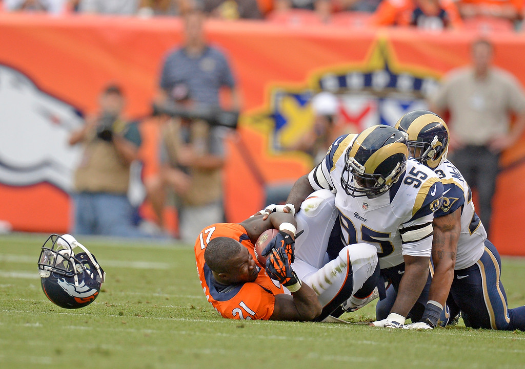 . DENVER, CO. - AUGUST 17: Denver Broncos running back Ronnie Hillman (21) gets tackled as his helmet flies after a tackle by St. Louis Rams defensive end William Hayes (95) during the first quarter August 24, 2013 at Sports Authority Field at Mile High. (Photo By John Leyba/The Denver Post)