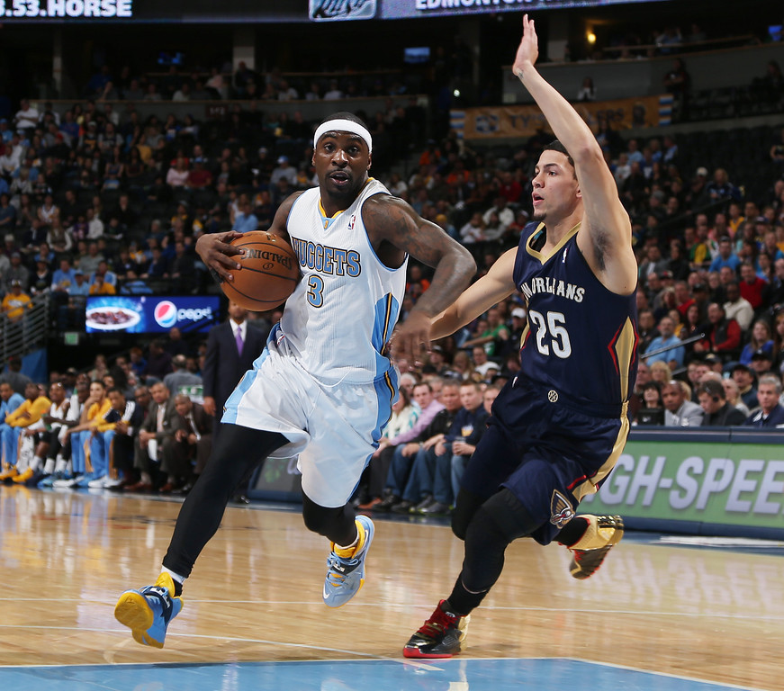 . Denver Nuggets guard Ty Lawson, left, drives lane for shot past New Orleans Pelicans guard Austin Rivers in the first quarter of an NBA basketball game in Denver on Sunday, Dec. 15, 2013. (AP Photo/David Zalubowski)