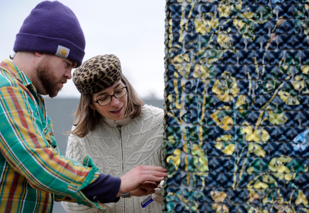 ". Artist Kim Dickey, right, and assistant Joshua Hebbert, unwrap ""Mille-fleur\"", her 20 foot ceramic wall covered in ceramic flowers. Artists and volunteers work on a new art installation, Catalyst: Colorado Sculpture at the Denver Botanic Gardens. (Photo By Kathryn Scott Osler/The Denver Post)"