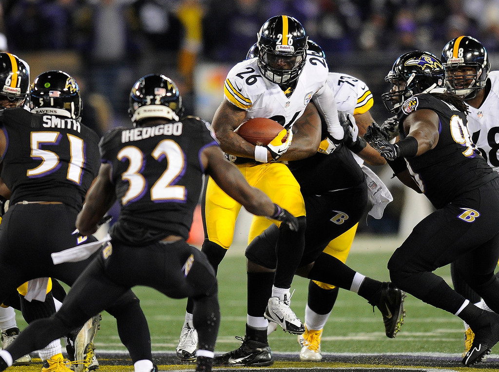 . Pittsburgh Steelers running back Le\'Veon Bell (26) tries to rush past Baltimore Ravens defenders in the first half of an NFL football game on Thursday, Nov. 28, 2013, in Baltimore. (AP Photo/Nick Wass)