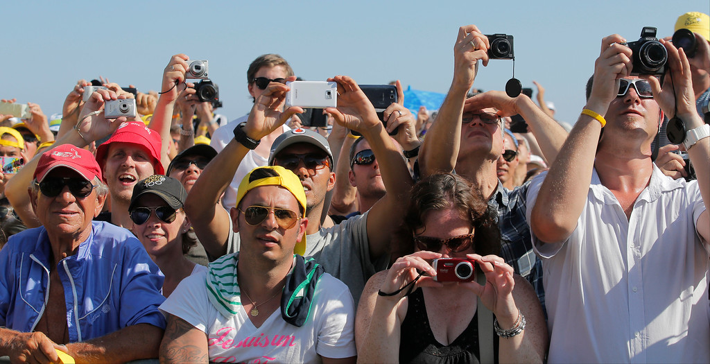. Spectators take images of the podium ceremony of the fourth stage of the Tour de France cycling race, a team time-trial over 25 kilometers (15.6 miles) with start and finish in Nice, southern France, Tuesday July 2, 2013. (AP Photo/Christophe Ena)