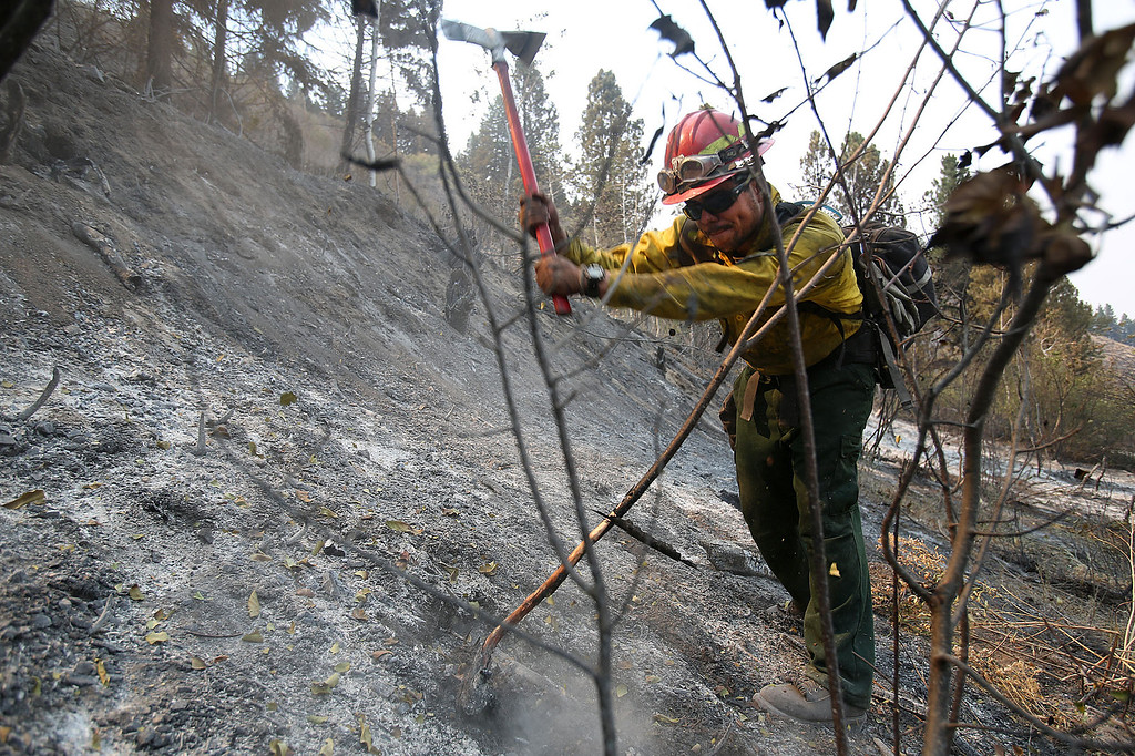 . Vincent Palato, with the Big Horn Basin Crew out of Cody, Wyo., mops up part of the 111,000 acre Elk Fire Complex near Pine, Idaho on Wednesday, Aug. 14, 2013. (AP Photo/Times-News, Ashley Smith)