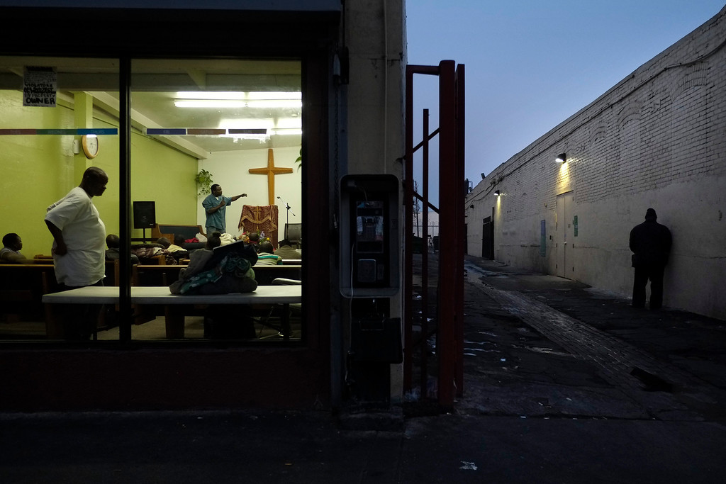 . Pastor Emmanuel Okoli, standing next to a cross, gives a sermon to homeless people at Outreach Mission Center as a man, right, urinates in an alley in the Skid Row area of Los Angeles, Thursday, March 21, 2013. The area, originally agricultural until the 1870s when railroads first entered Los Angeles, has maintained a transient nature through the years from the influxes of short-term workers, migrants fleeing economic hardship during the Great Depression, military personnel during World War II and the Vietnam conflict, and low-skilled workers with limited transportation options who need to remain close to the city\'s core, according to the Los Angeles Chamber of Commerce. (AP Photo/Jae C. Hong)