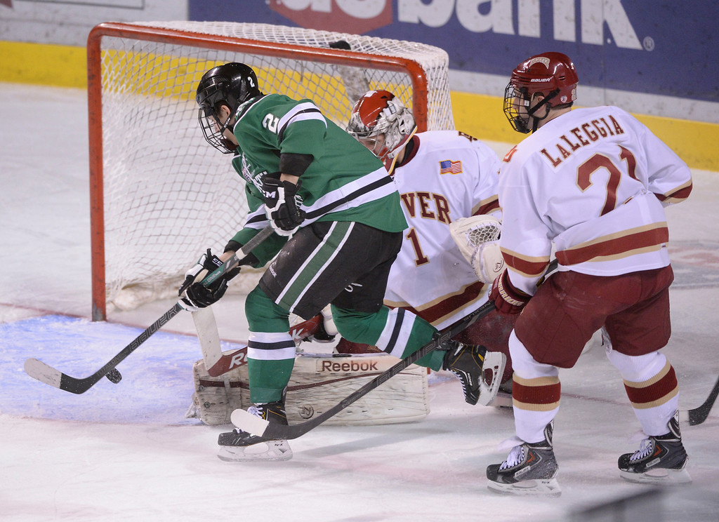 . DENVER, CO. - JANUARY 24:  North Dakota defenseman Troy Stecher (2) chased a puck through the crease in front of Denver goalie Sam Brittain (1) in the third period. The University of Denver hockey team hosted North Dakota at Magness Arena Friday night, January 24, 2014. Photo By Karl Gehring/The Denver Post