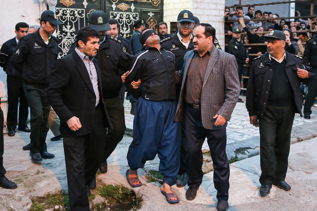. Balal (C), who killed an Iranian youth Abdolah Hosseinzadeh in a street fight with a knife in 2007, is brought to the gallows by judicial officals during his execution ceremony in the northern city of Nowshahr on April 15, 2014.  AFP PHOTO/ARASH KHAMOOSHI/AFP/Getty Images