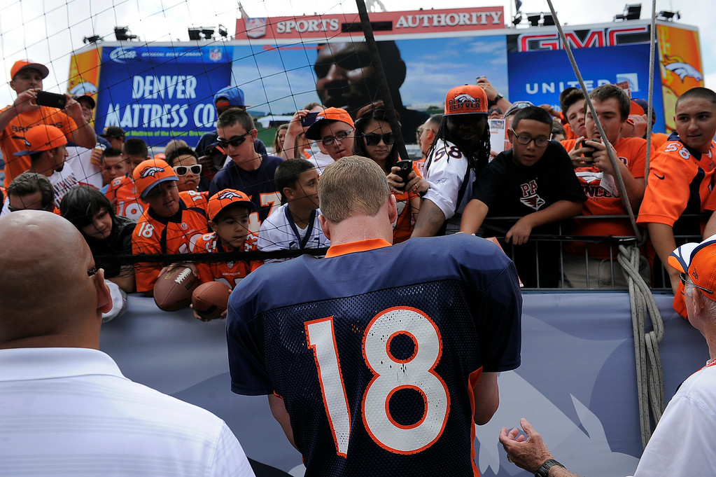 . Denver Broncos quarterback Peyton Manning (18) signs autographs for fans on day four of the Denver Broncos 2014 training camp July 27, 2014 at Sports Authority Field at Mile High. (Photo by John Leyba/The Denver Post)
