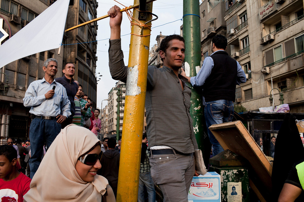 . People look on as members of a journalists\' union march to Tahrir Square during protests in Cairo, Nov. 27, 2012. Demonstrators began flowing into the streets of Cairo Tuesday for a day of protest against President Mohammed Morsi\'s effort to assert broad new powers, dismissing his efforts only hours before to reaffirm his deference to Egyptian law and courts. (Ivor Prickett/The New York Times)