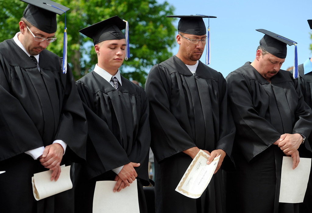 . Bowing their heads in prayer during the benediction are graduates from left to right, Ryan Tate, Ryan Ruybal, Alfredo Martinez, and David Gorry. (Photo By Kathryn Scott Osler/The Denver Post)