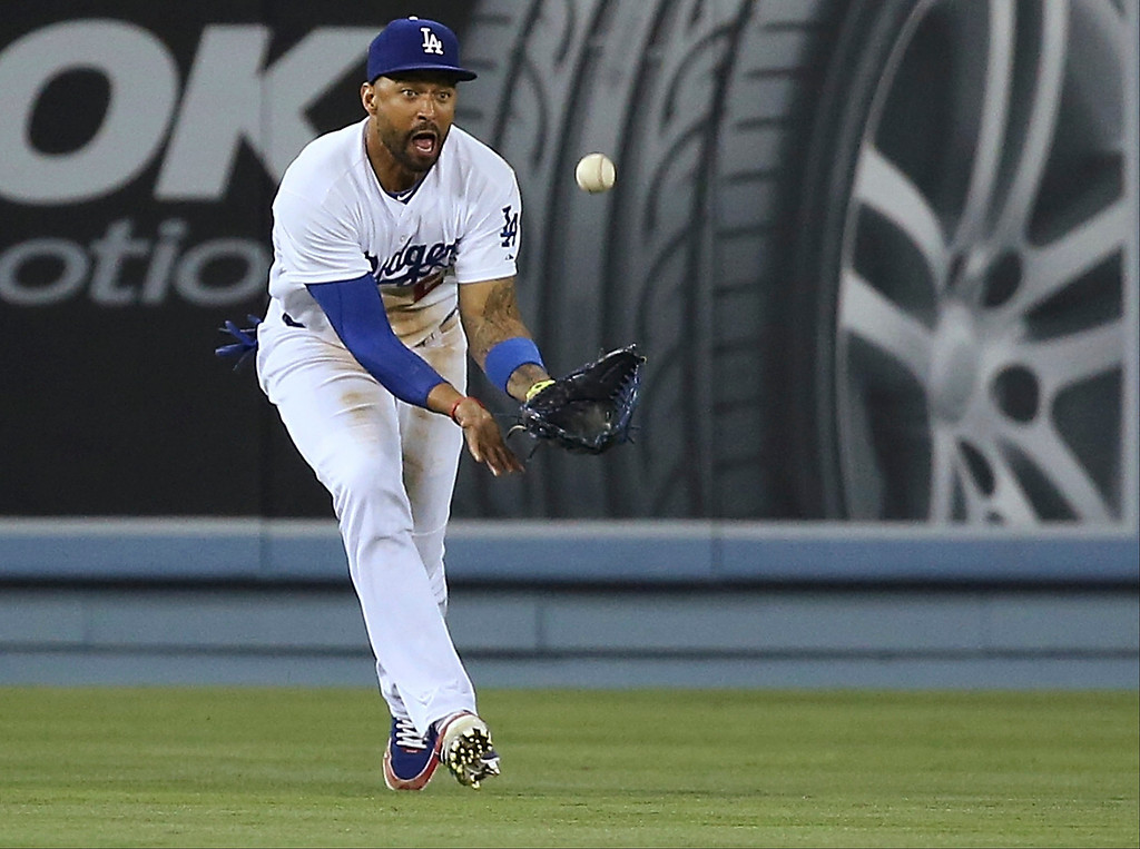 . LOS ANGELES, CA - JUNE 16:  Matt Kemp #27 of the Los Angeles Dodgers gets his glove under a fly ball for the third out in the sixth inning during the MLB game against the Colorado Rockies at Dodger Stadium on June 16, 2014 in Los Angeles, California.  (Photo by Victor Decolongon/Getty Images)