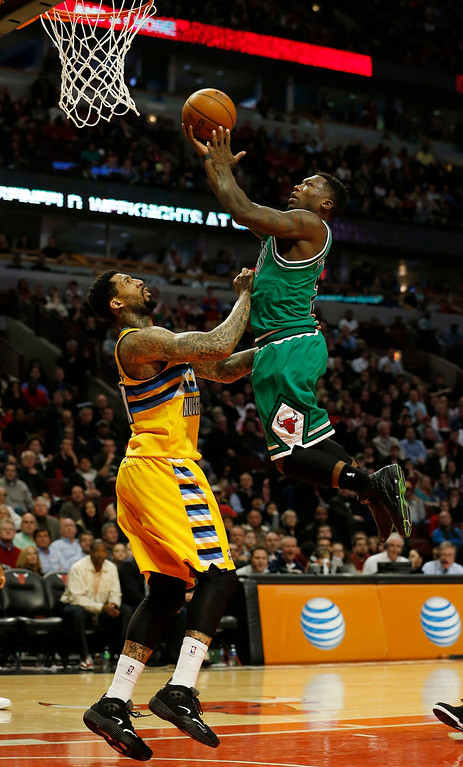 . Chicago Bulls\' Nate Robinson (R) goes to the basket against Denver Nuggets\' Wilson Chandler during the overtime of their NBA basketball game in Chicago, Illinois March 18, 2013. REUTERS/Jim Young