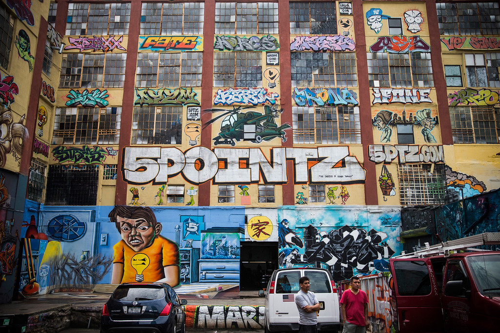 ". NEW YORK, NY - AUGUST 09:  People stand near the ""5 Pointz\"" building on August 9, 2013 in the Long Island City neighborhood of the Queens borough of New York City. 5 Pointz is a series of properties that graffiti artists use as an outdoor art exhibit space - it is considered the Mecca of the graffiti world. The space has been used as a space for graffiti artists since the early 1990s, though in 2011, Jerry Wolkoff, the owner of the property, announced he planned to demolish the building to build high-rise residential buildings. The 5 Pointz graffiti community has since been in a battle to keep the space as is; they are currently petitioning the government to consider the space a protected cultural landmark.  (Photo by Andrew Burton/Getty Images)"