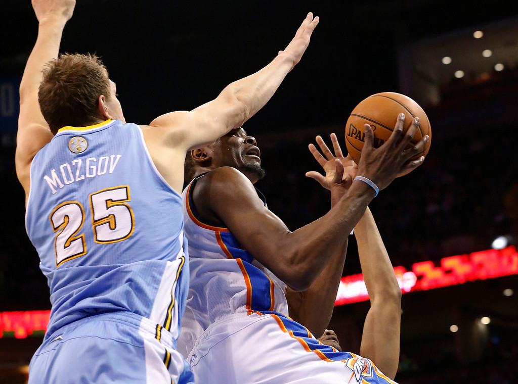 . Oklahoma City Thunder forward Kevin Durant (35) is fouled by Denver Nuggets center Timofey Mozqov (25) as he shoots in the third quarter of an NBA basketball game in Oklahoma City, Monday, March 24, 2014. Oklahoma City won 117-96.(AP Photo/Sue Ogrocki)