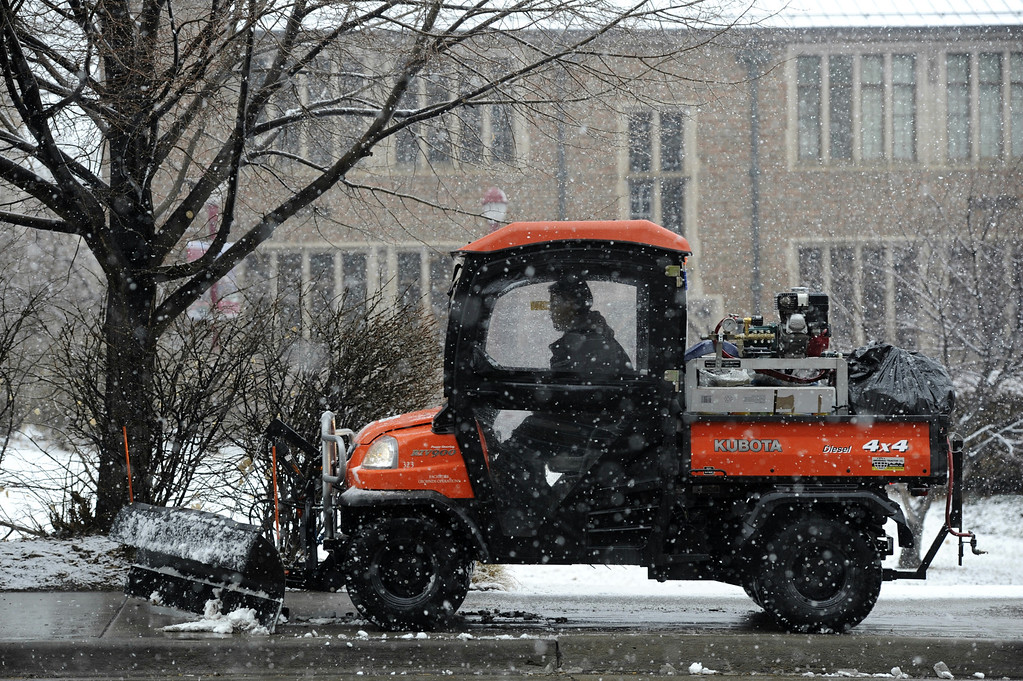 . A worker clears a small amount of now of a sidewalk along University Blvd nears Evan Ave at the University of Denver Saturday  morning,  March 9th, 2013. Andy Cross, The Denver Post