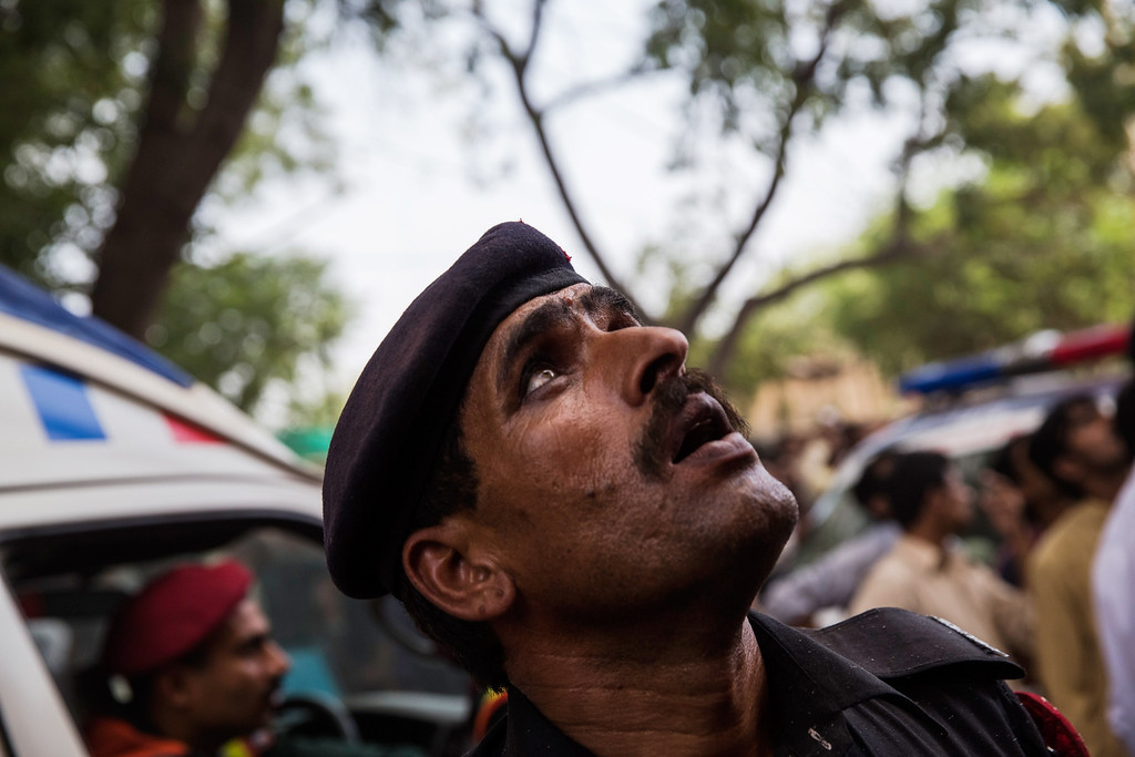 . A policeman watches as rescue workers attempt to reach people trapped as a fire takes hold at the Lahore Development Authority (LDA) Plaza on May 09, 2013 in Lahore, Pakistan.  (Photo by Daniel Berehulak/Getty Images)