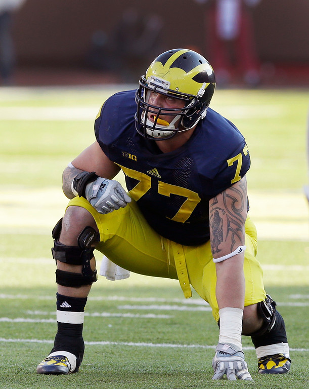 . In this Nov. 30, 2013, file photo Michigan offensive linesman Taylor Lewan (77) gets set during the second half of an NCAA college football game against Ohio State in Ann Arbor, Mich. Lewan was selected by the Tennessee Titans in the first round, 11th overall, in the NFL draft on Thursday, May 8, 2014. (AP Photo/Carlos Osorio)