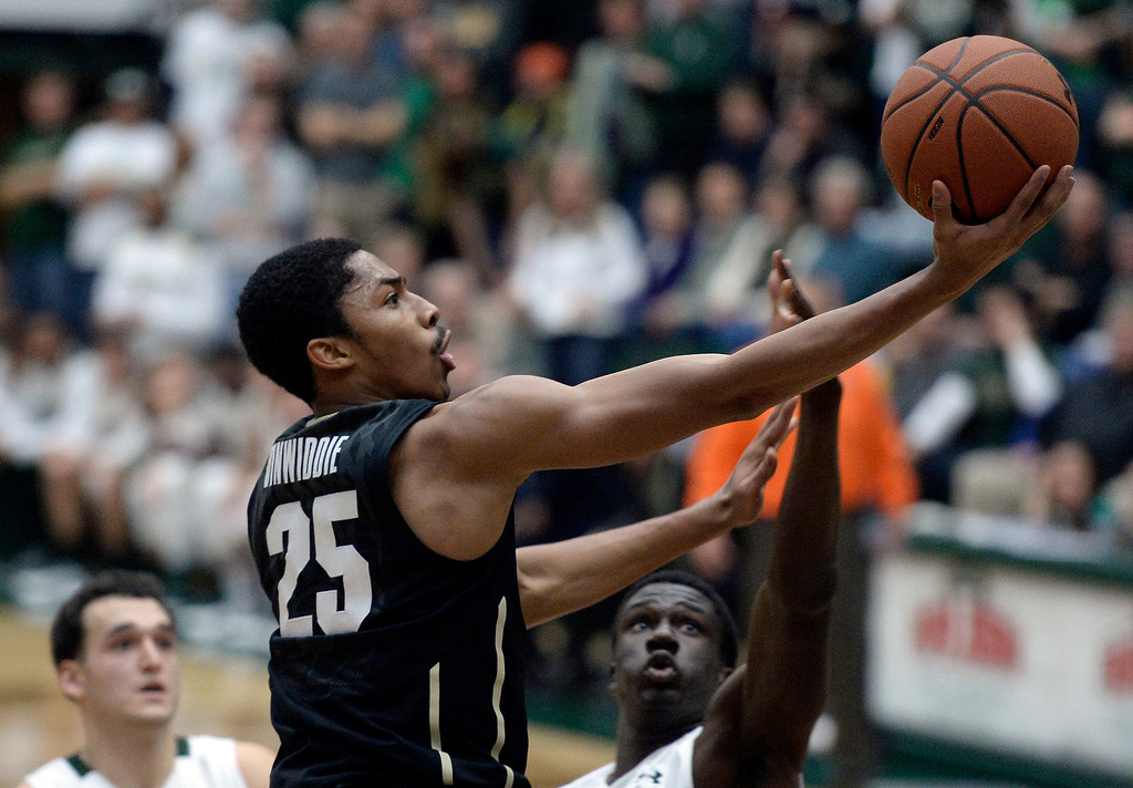 . CU\'s Spencer Dinwiddie drives to the hoop to score in front of Joe De Ciman, at right, and J.J. Avila, at left, during an NCAA game against CSU on Tuesday, Dec. 3, 2013, at the Moby Arena in Fort Collins.