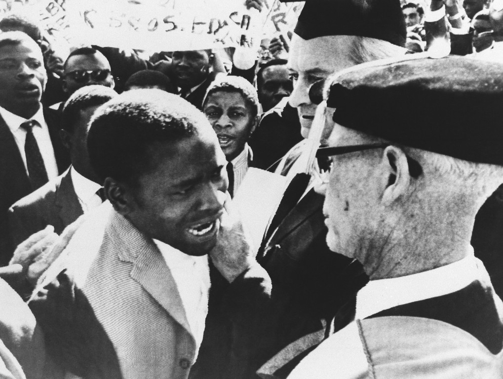 . Professor J.P. Duminy, Vice Chancellor, foreground, of the Cape Town University (South Africa) is seen confronted by an angry demonstrating African students on Saturday, July 16, 1966 at the University College of Rhodesia, Salisbury, Zimbabwe. The flare-up started when white and black students clashed as a group of Africans tried to stop the graduation ceremony on the campus of the University, waving banners the students jostled whites around until they were finally broken up. During the ceremony they drowned white speakers be singing African nationalist songs. (AP Photo)