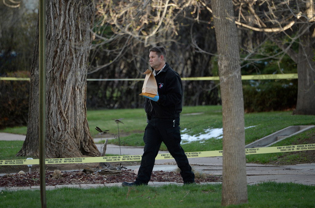 . A man carries out evidence as Denver police investigate a homicide at a home in the 2100 block of South Saint Paul Street in Denver, Tuesday, April 15, 2014.  (Photo by RJ Sangosti/The Denver Post)