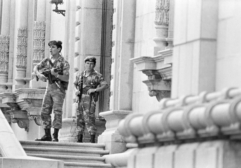 . Two Guatemalan soldiers stand guard on the steps of the Presidential Palace in Guatemala City, Aug. 10, 1983, one day after the government of Gen. Efrain Rios Montt was toppled by a military coup. (AP Photo/P.W. Hamilton)