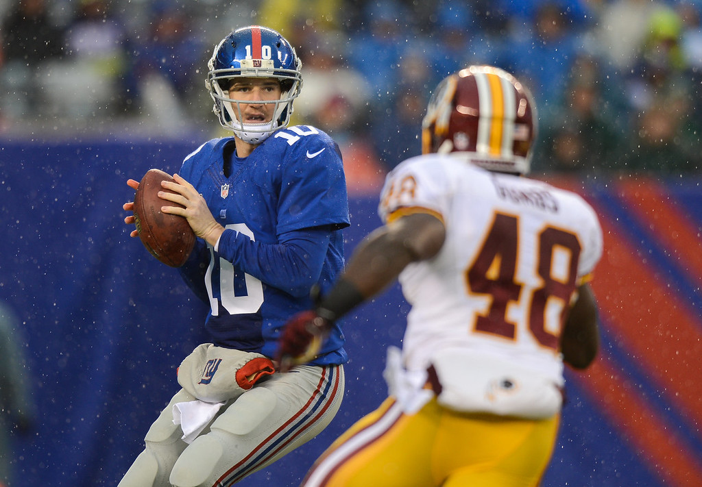 . Quarterback Eli Manning #10 of the New York Giants under pressure from strong safety Jose Gumbs #48 of the Washington Redskins in the first half  at MetLife Stadium on December 29, 2013 in East Rutherford, New Jersey. (Photo by Ron Antonelli/Getty Images)