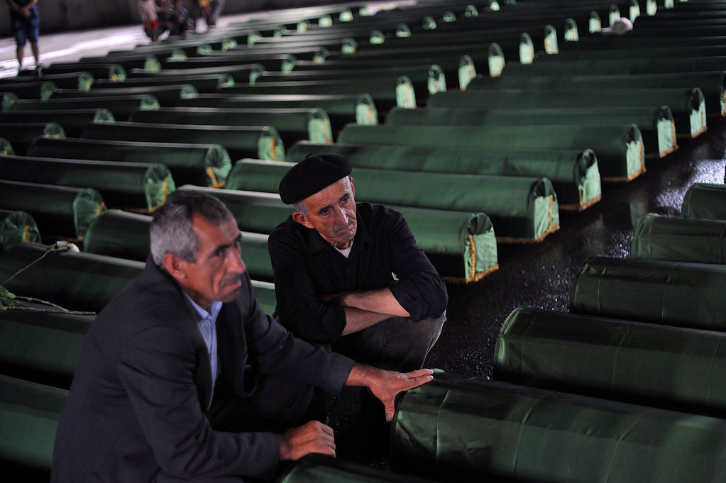 . Bosnian Muslims, survivors of Srebrenica 1995 massacre, pray and cry near body caskets of their relatives, laid out in a factory hangar, near memorial cemetery in village of Potocarion near Eastern-Bosnian town of Srebrenica, on July 10, 2013. Potocari Memorial cemetery is undergoing preparations for another mass burial on July 11, when 409 newly identified bodies will be put to final rest. Bodies are identified as those belonging to Bosnian Muslim victims, of the offensive undertaken by Bosnian Serbs in July 1995 with aim to occupy, earlier declared UN safe heaven area of Srebrenica and the surrounding villages. During the offensive more than 8.000 Bosnian non-Serbs went missing to be found buried in mass graves, years after the war ended.  ELVIS BARUKCIC/AFP/Getty Images