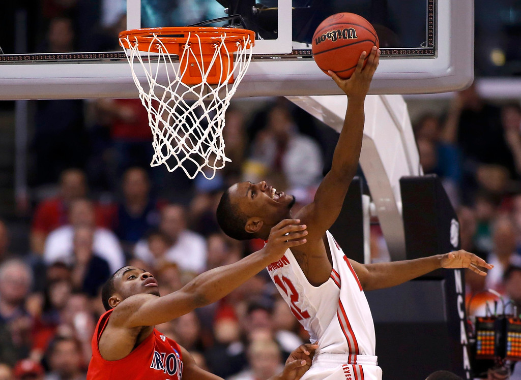 . Ohio State Buckeyes forward Sam Thompson (12) scores from behind the basket on Arizona Wildcats\' Kevin Parrom (3) during the second half in their West Regional NCAA men\'s basketball game in Los Angeles, California March 28, 2013.  REUTERS/Danny Moloshok