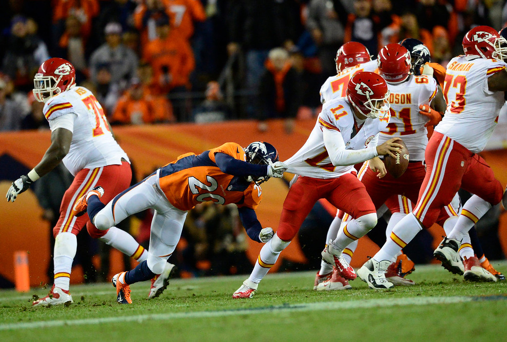 . Kansas City Chiefs quarterback Alex Smith (11) breaks a tackle by Denver Broncos strong safety Mike Adams (20) and throws the ball away in the second quarter. The Denver Broncos take on the Kansas City Chiefs at Sports Authority Field at Mile High in Denver on November 17, 2013. (Photo by AAron Ontiveroz/The Denver Post)