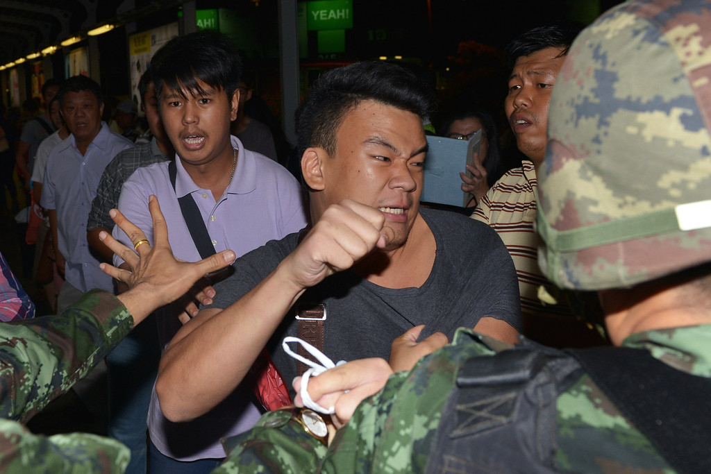 . A protester scuffles with army soldiers while resisting arrest after an anti-coup rally on May 23, 2014 in Bangkok, Thailand. Several hundred anti-coup protesters rallied in Bangkok\'s shopping district, a day after the military seized control in a bloodless coup. (Photo by Rufus Cox/Getty Images)