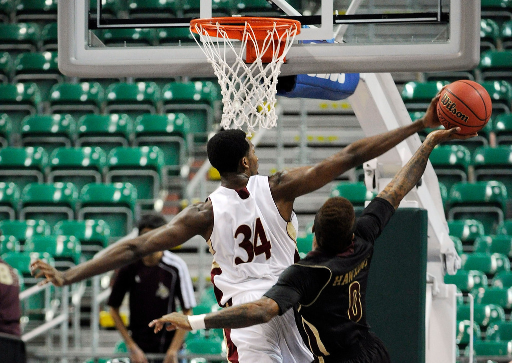 . Denver\'s Chris Udofia (34) blocks a shot by Texas State\'s Phil Hawkins (0) during the second half of a Western Athletic Conference tournament NCAA college basketball game on Thursday, March 14, 2013 in Las Vegas. Texas State won 72-68. (AP Photo/David Becker)