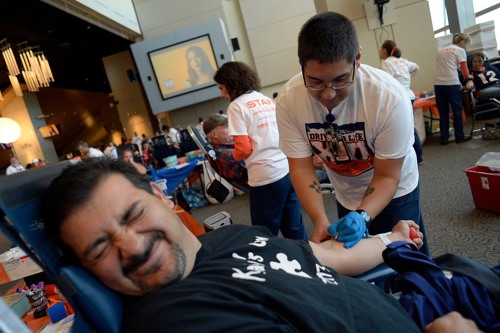 """. DENVER, CO - OCTOBER 22: Jeff Vigil 38 of Thornton grimaces as he gets poked with a needle by William Lopez during The Denver Broncos and Bonfils Blood Center\'s 16th annual Drive for Life community blood drive October 22, 2013 at Sports Authority Field. Jeff doesn\'t like needles as he said \""""Oh Sweet Jesus\"""" as Lopez inserted the needle. (Photo by John Leyba/The Denver Post)"""
