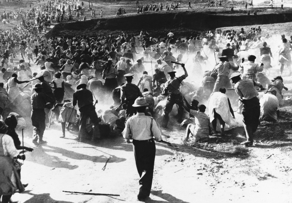 . South African police beat African women with clubs in Durban in 1959, when the women raided and set fire to a beer hall in protest against police action against their home brewing activities. South Africa\'s racial segregation policies still trouble the nation. (AP Photo)