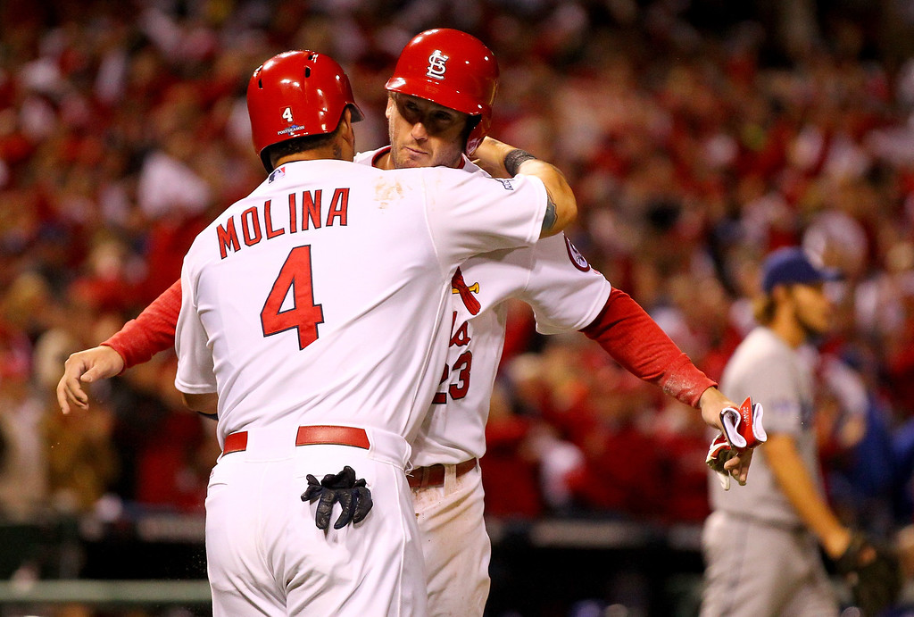 . ST LOUIS, MO - OCTOBER 18:  Yadier Molina #4 and David Freese #23 of the St. Louis Cardinals celebrate after both scoring in the third inning against the Los Angeles Dodgers in Game Six of the National League Championship Series at Busch Stadium on October 18, 2013 in St Louis, Missouri.  (Photo by Dilip Vishwanat/Getty Images)