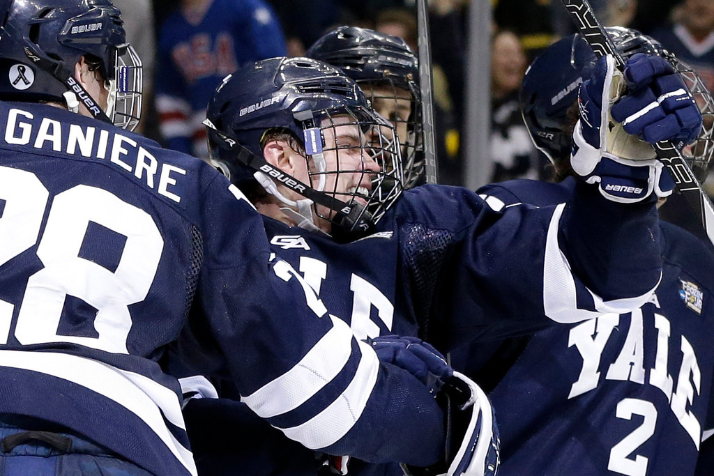 . Yale\'s Clinton Bourbonais, center, celebrates after his goal during the first period of the NCAA men\'s college hockey Frozen Four national championship game against Quinnipiac in Pittsburgh, Saturday, April 13, 2013. (AP Photo/Gene Puskar)