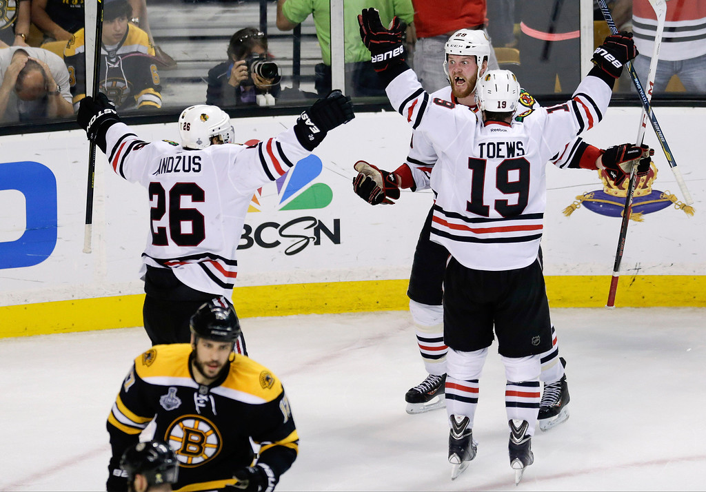 . Chicago Blackhawks left wing Bryan Bickell, center, celebrates his goal with Chicago Blackhawks center Jonathan Toews (19) and Chicago Blackhawks center Michal Handzus (26), of Slovakia, during the third period in Game 6 of the NHL hockey Stanley Cup Finals against the Boston Bruins, Monday, June 24, 2013, in Boston. (AP Photo/Charles Krupa)
