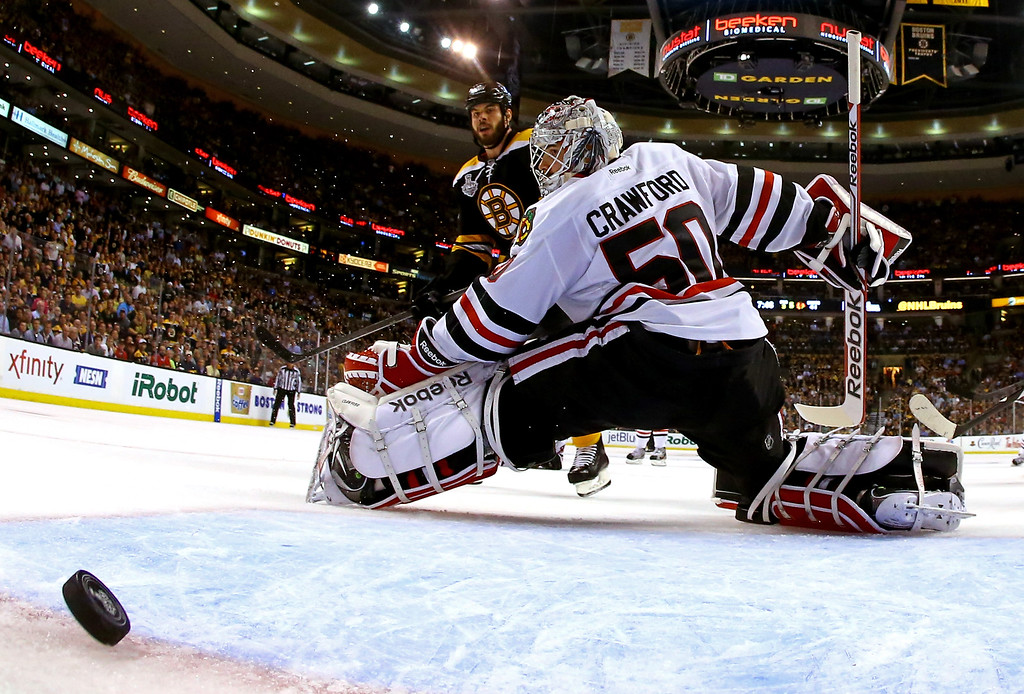 . Johnny Boychuk #55 of the Boston Bruins scores a goal against Corey Crawford #50 of the Chicago Blackhawks during the third period in Game Four of the 2013 NHL Stanley Cup Final at TD Garden on June 19, 2013 in Boston, Massachusetts.  (Photo by Harry How/Getty Images)