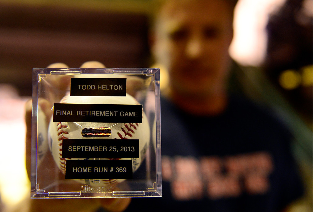 . Dylan Casey, who caught Todd Helton\'s first-inning home run, displays a commemorative replacement given to him by the Rockies during the action in Denver. The Colorado Rockies hosted the Boston Red Sox and said farewell to longtime first baseman Todd Helton, who recently announced his retirement following this season. (Photo by AAron Ontiveroz/The Denver Post)