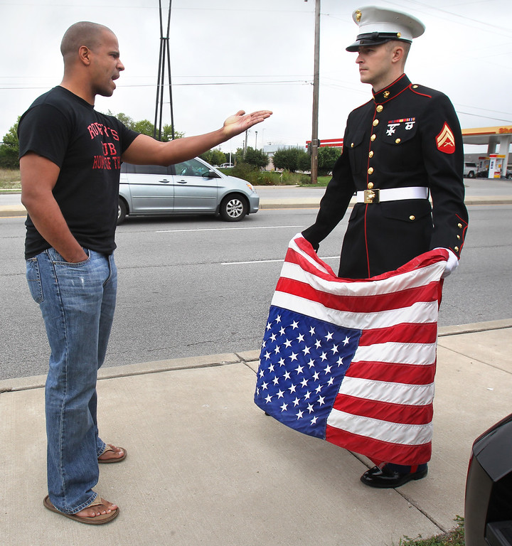 """. Beech Grove resident Joseph Lohman, 25, right, who served as a corporal in the U.S. Marines from 2008-2012, is confronted by Southside Indianapolis Marine recruiter Sgt. Joshua York, left, as Lohman stands alongside South Emerson Avenue holding an upside down American flag, a signal of distess, to show his concern over the government shutdown that started at midnight. \""""With the flag upside down, it means that the country is in distress,\"""" says Lohman, who headed out onto the sidewalk at midnight. He said he is concerned about veterans not getting their disability checks with the government shut down.  (AP Photo/The Star,Charlie Nye)"""