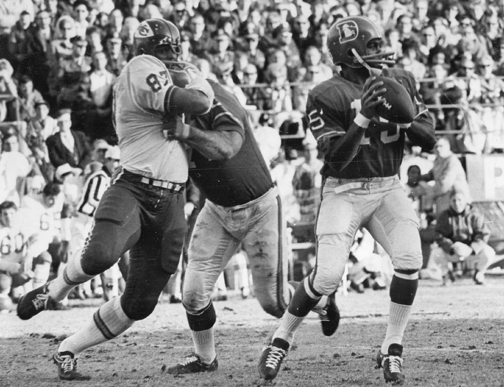. Denver quarterback Marlin Briscoe is unaware that a battle is occurring behind him in the first quarter Saturday. Denver\'s Sam Brunelli is shown holding Kansas City\'s Aaron Brown while Briscoe prepares to let loose with a pass. 1968.   (Photo by Bill Johnson/Denver Post)